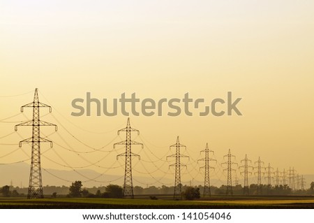 Transmission line at sunset with clear orange sky and no end pylons