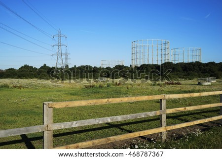 Transmission tower and Gas Holder in the countryside on bright sunny day