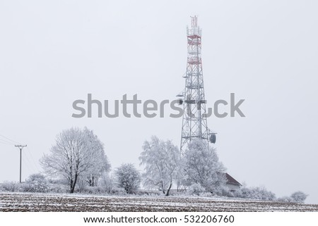 Transmission tower in winter, Telecommunications tower with cellular antenna and satellite dish