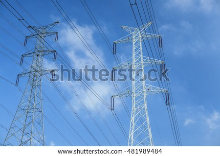 Transmission towers against blue sky