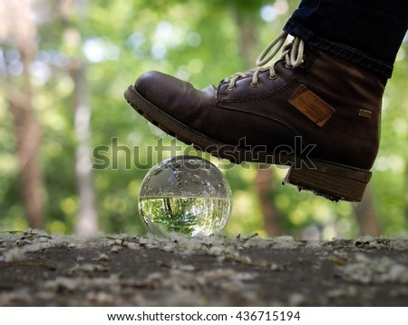 Transparent ball under heavy muddy boots. The path, the forest. The boot falls on the fragile balloon. Concept, idea