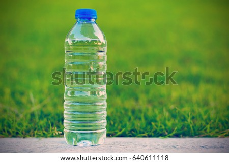 Transparent bottle with clean water on green grass background - health life concept
