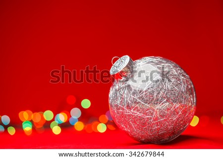 Transparent Christmas bauble filled with silver tinsel on red background with blurred christmas lights - stock photo