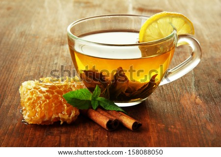 Transparent cup of green tea with honey and cinnamon on wooden background - stock photo