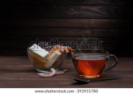 Transparent cup of tea and sweets on a wooden background - stock photo
