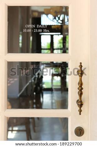 Transparent door of vintage restaurant open daily 10.00 - 23.00 Hrs. - stock photo