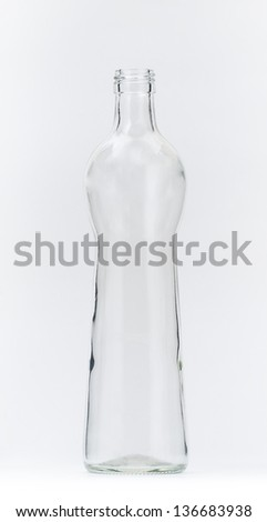 Transparent glass bottle, studio shot on grey background - stock photo