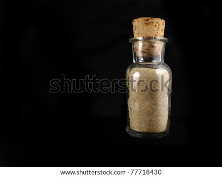 transparent glass bottle with sand and a brown bottom - stock photo