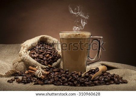 Transparent  glass coffee cup and coffee beans on burlap textile and brown background. - stock photo