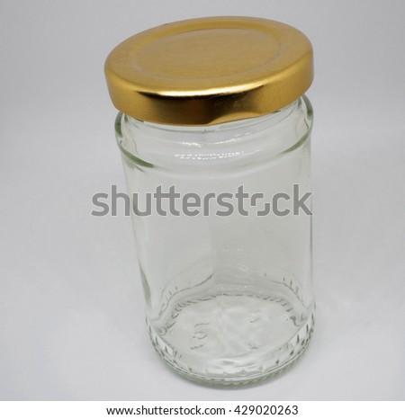 Transparent glass jar isolated on white background, with the closed gold color lid