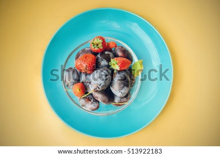 Transparent glass salad bowl with plums and strawberries on a blue flat plate