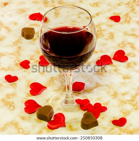 Transparent glass with red wine, heart shape chocolate and textile red valentine hearts, old paper background, close up. - stock photo