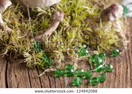 Transparent green glass beads with mushrooms and green moss on old wooden table - stock photo