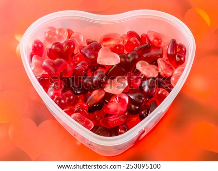 Transparent heart shape vase (bowl) filled with colored (red) heart shape jellies, red bokeh background, close up - stock photo