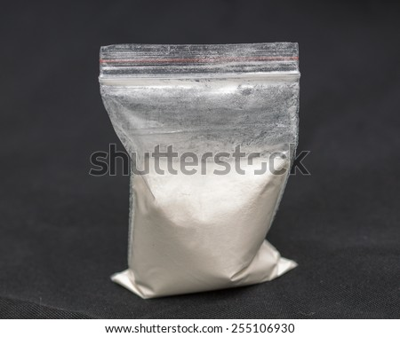 Transparent plastic bags with white powder isolated on black background  - stock photo