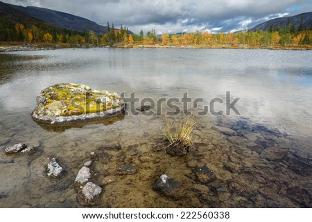 Transparent Polygonal lake bottom with lichen-covered rocks and colorful northern taiga forest in foreground - stock photo