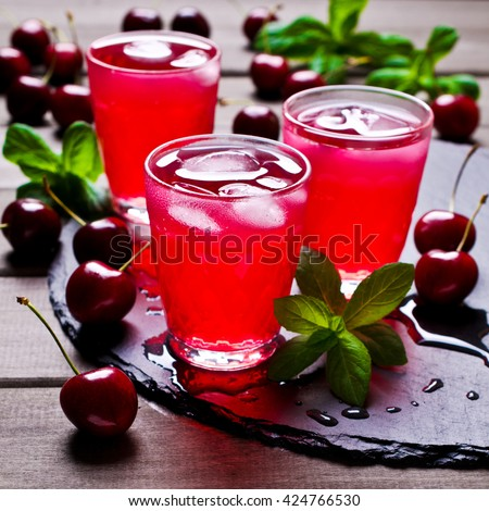 Transparent red drink made from cherries on a wooden background. Selective focus. - stock photo