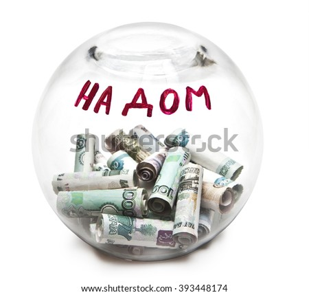 """Transparent round piggy Bank with money and the inscription in Russian """"on the house"""" - stock photo"""