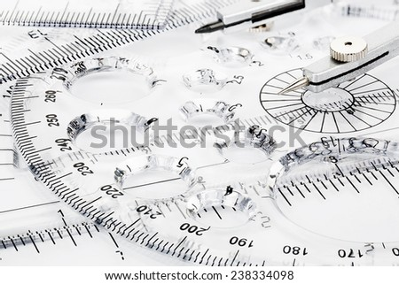 transparent rulers and pair of compasses closeup - stock photo