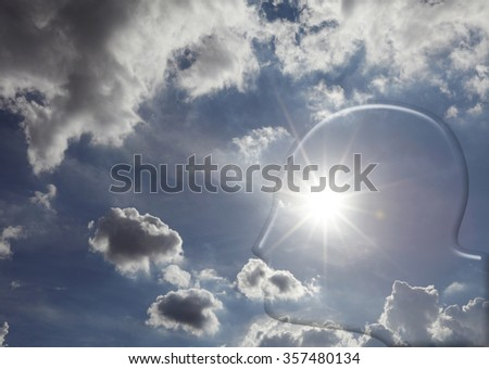 Transparent silhouette of a man's head in a blue cloudy sky with a sun-burst as eye for the concept of imagination. - stock photo