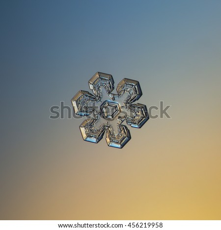 Transparent snowflake on smooth blue / orange gradient background. This is macro photo of real snow crystal with simple shape, but complex inner pattern and glossy surface.