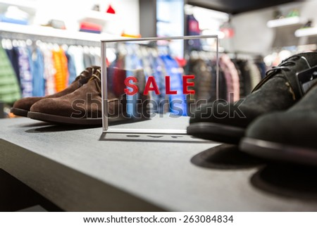 Transparent table with SALE inscription on it standing on a demonstration desk  - stock photo
