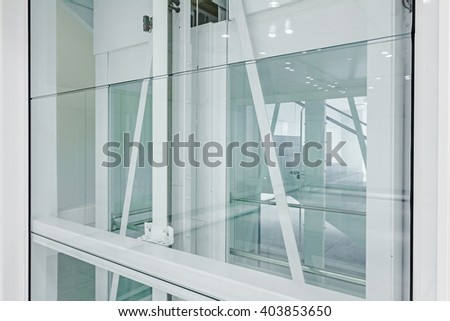 Transparent walls in elevator and staircase in modern building.
