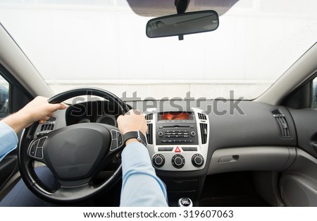 transport, business trip, destination and people concept - close up of young man driving on car parking