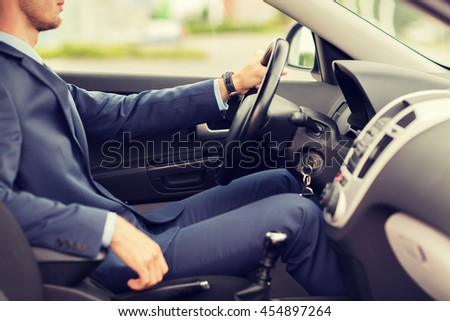 transport, business trip, destination and people concept - close up of young man in suit driving car - stock photo