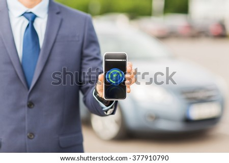 transport, business trip, ecology, technology and people concept - close up of man showing smartphone eco mode icon on screen on car parking - stock photo