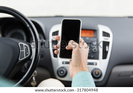 transport, business trip, technology and people concept - close up of young man hand with smartphone driving car - stock photo