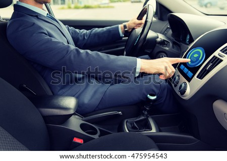 transport, business trip, technology and people concept - close up of young man in suit driving car and adjusting car eco mode system settings on dashboard computer screen