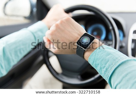 transport, business trip, technology, time and people concept - close up of man with engine start button on smart watch driving car - stock photo