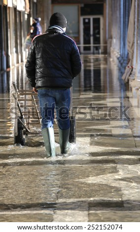 transport cart and man with green boots at high tide in Venice