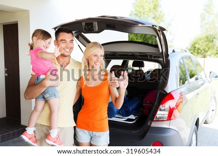 transport, leisure, road trip and people concept - happy family with little girl sitting on trunk of hatchback car and waving hands at home parking space - stock photo