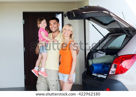 transport, leisure, road trip, travel and people concept - happy family with little girl packing things hatchback car at home parking space - stock photo