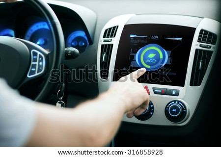 transport, modern, green energy, technology and people concept - male hand using car eco system mode - stock photo