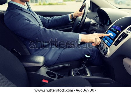 transport, modern technology and people concept - close up of young man in suit driving car and pointing finger to car icon on board computer screen