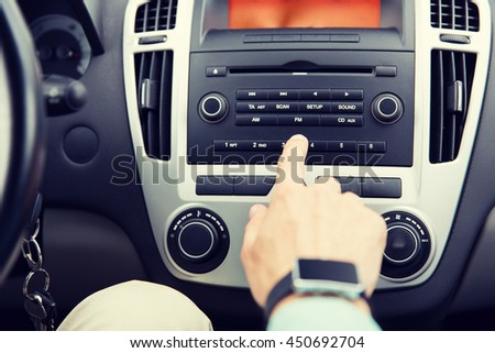 transport, road trip, car driving, technology and people concept - close up of male hand turning on radio on control panel system in car - stock photo