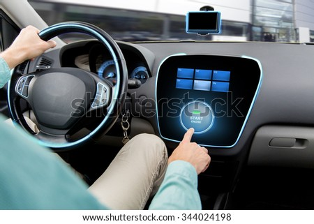 transport, road trip, car driving, technology and people concept - close up of man driving car and pushing start engine button on board computer - stock photo