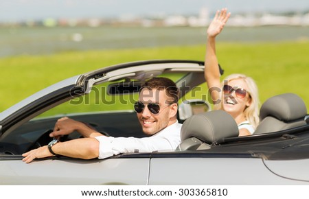transport, road trip, leisure, gesture and people concept - happy man and woman driving in cabriolet car and waving hand - stock photo