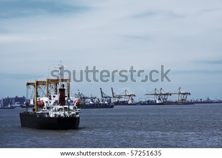 Transport ship on sea, cranes and harbor in background