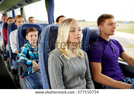 transport, tourism, road trip and people concept - happy couple with group of passengers or tourists in travel bus