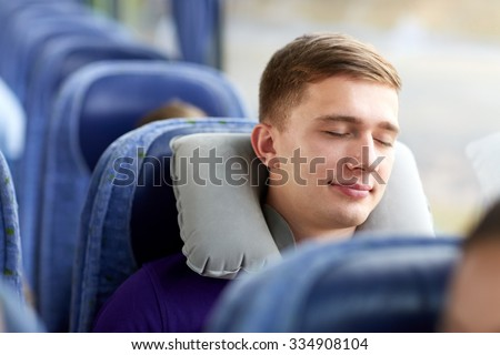 transport, tourism, road trip and people concept - happy young man sleeping in travel bus with pillow - stock photo