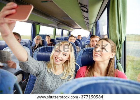 transport, tourism, road trip and people concept - happy young women or friends in travel bus taking selfie by smartphone - stock photo