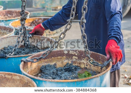 Transport workers are carrying sludge treatment system through a rolled sheet to take to eradicate the plant. - stock photo