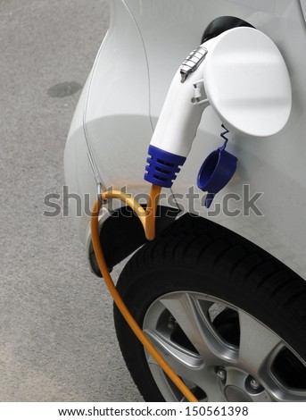 Transportation and environment concept. Close-up image of a ecological green energy electric eco car parking at urban street during battery charge. - stock photo
