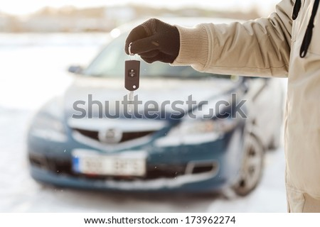 transportation and ownership concept - closeup of man hand with car key outdoors - stock photo