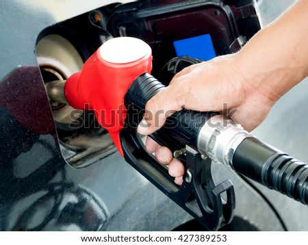 transportation and ownership concept, Closeup of man pumping gasoline fuel in car at gas station.