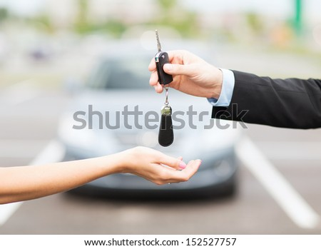 transportation and ownership concept - customer and salesman with car key outside